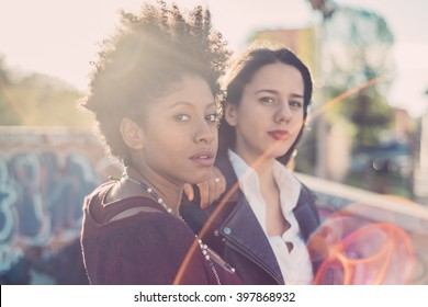 Half length of two young multiethnic friends outdoor in the city back light, looking in camera - friendship, woman power, serenity concept