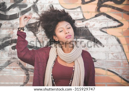 half length of a  young beautiful black curly hair african woman lenaning against a wall in town, with eyes closed, smiling - youth, carefreeness, relaxing concept