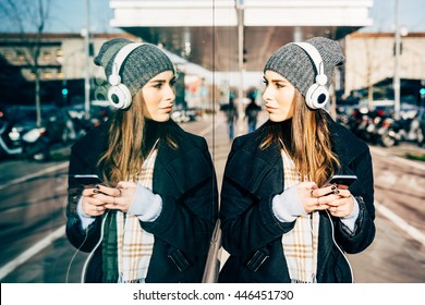 Half length of young beautiful caucasian woman listening music with headphones and smartphone handhold looking in the mirror leaning on a reflected surface wall - music, technology, reflection concept