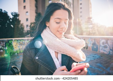 Half length of young beautiful long hair woman in city back light using smartphone tapping touchscreen smiling - technology, social network, communication concept