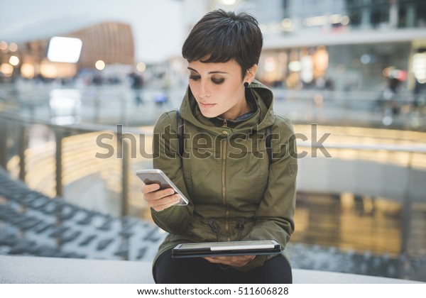 Half length of young handsome caucasian brown straight hair woman using smartphone and tablet, looking downward screen, smiling - multitasking, technology, social network concept concept