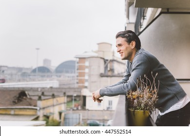 Half length of young handsome man standing on a balcony outdoor, overlooking, happy - positive, carefree, thinking future concept