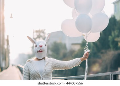 Half length of young millennial woman wearing rabbit mask holding white balloon - carnival, dreamlike, surreal concept