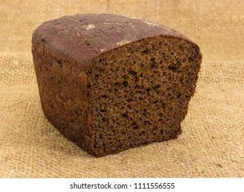 Half of loaf of the brown rye and wheat bread  with added rye malt and coriander on a sackcloth