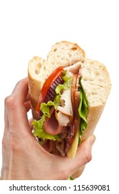 Half of long tasty subway baguette sandwich with lettuce, tomatoes, ham, turkey breast, salami and cheese isolated on white background