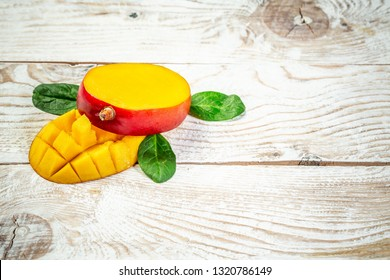 half of Mango fruit decorated with leaves. sliced mango chunks on wooden background, copy space text, blank for text, top view.