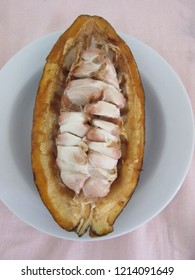 Half of mature cocoa arranged longitudinally in a white dish, viewed from above