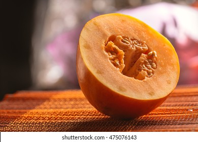 Half of melon on a dark wooden and blurred background