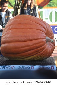 HALF MOON BAY, CA - OCTOBER 2015 - Kids stand next to a giant pumpkin at the 45th annual Pumpkin Weigh-Off contest in Half Moon Bay, California.