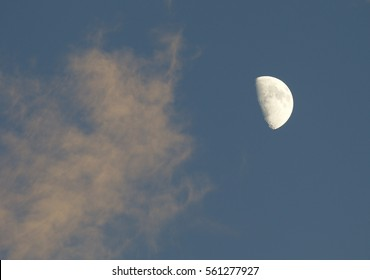 Half Moon in blue sky with passing clouds; very nice sharp crater detail