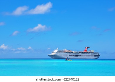 Half Moon Cay, Bahamas – July 23, 2013: Carnival Cruise Line, cruise ship Carnival Extasy anchored near beautiful island Half Moon Cay while the tourists are enjoying sunny day at the beach