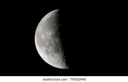 Half moon concept. Half moon on black background. It is a black and white image that see details on the surface. Look again is awesome suitable for background. Moon orbit planet Earth.