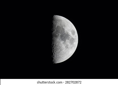 Half moon during the first quarter phase isolated against a black sky.
