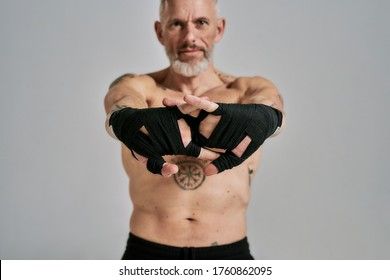 Half naked middle aged athletic man, kickboxer stretching hands standing in studio over grey background. Muay Thai, Boxing or Kickboxing concept. Focus on hands. Front view. Horizontal shot