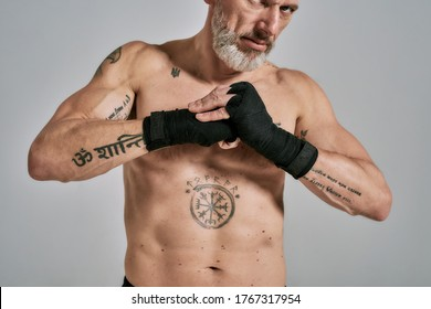 Half naked middle aged athletic man, kickboxer warming up wrapped hands before training standing in studio over grey background. Muay Thai, Boxing or Kickboxing concept