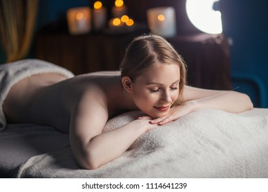 Half naked woman resting after massage in cool room