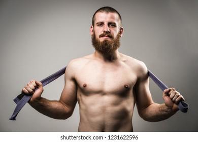 Half Necked Male Athlete holding BJJ Belt
