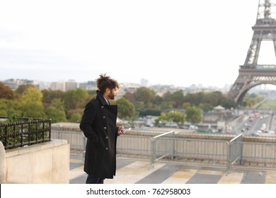 Half Nigerian guy near Eiffel Tower sends messages to girlfriend using modern smartphone in slow motion. Handsome jocund man wears black coat, ring with white stone and earring, has dark hair, beard