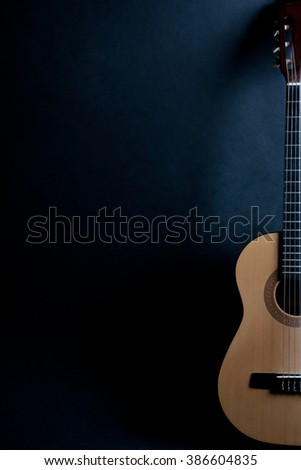 Half of an old acoustic guitar on a black background (with copy space)