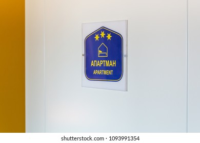 "Half open door of studio apartment with three stars. Letter on Serbian language ""APARTMAN"" means APARTMENT."