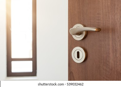 Half opened door to a empty room. Door handle, door lock. Welcome, to new home concept