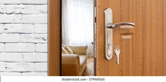Half opened door handle closeup, entrance to a living room. Welcome, privacy concept. Door lock with keys, white brick wall, modern interior design.