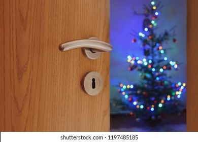 Half opened door into the cozy home Christmas interior