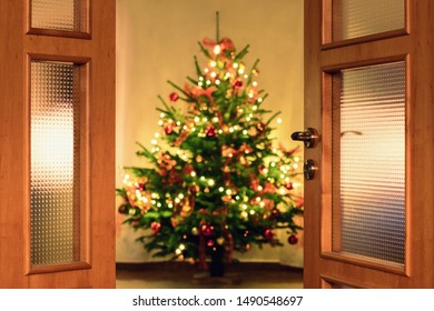 Half opened door into the cozy home  interior with beautiful Christmas tree - blured lights