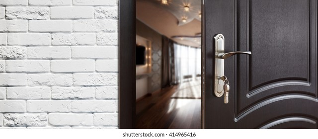 Half opened door to a living room. Door handle, door lock. Lounge door half open. Opening door. Welcome, privacy concept. Entrance to the room. Door at white brick wall, modern interior design.