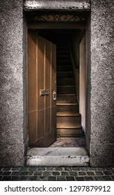 Half opened door showing a wooden stairway inside an old house, blur