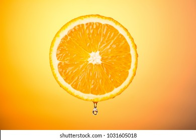 half an orange with a drop of water on a colored background, concept healthy eating citrus fruit