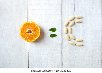 Half orange with leaves and letter C made from pills on white wood .Vitamins from fruit concept.