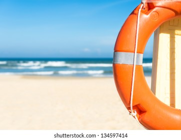 Half of orange lifebuoy in foreground. Blue clear sky, sea and sand in background. Bright sunny day. Holidays at beach. Beautiful seascape. Equipment for rescue of people. Service for lifesaving.