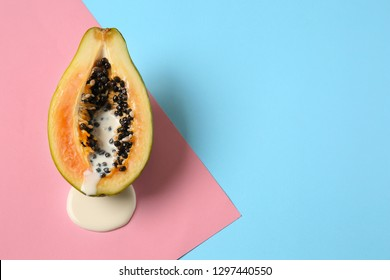 Half of papaya with dripping white liquid on color background. Erotic concept