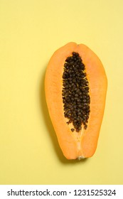 half papaya fruit on seamless yellow background, with blank space
