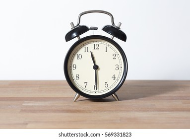 It is half past eleven. The time is 11:30 am or pm. Eleven thirty o'clock. Retro clock isolated on a wooden table. White background. Copy space.