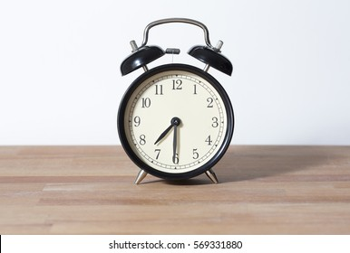 It is half past seven. The time is 7:30 am or pm. Seven thirty o'clock. Retro clock isolated on a wooden table. White background. Copy space.