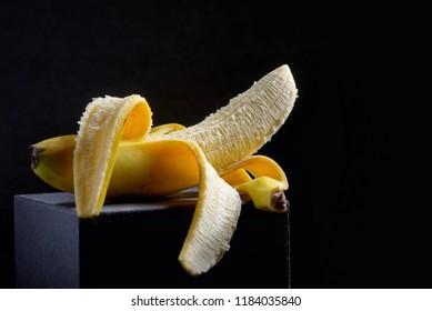 Half peeled banana on black background