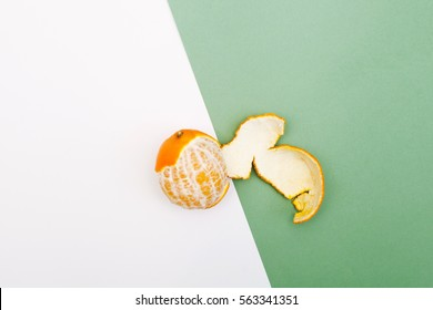 Half peeled fresh orange on a white and green background, top view minimalistic