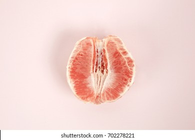a half peeled grapefruit on a pop colored background. Minimal color still life and quirky photography