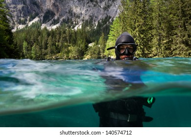 Half half photo of Scuba Diver in the lake Gruner in Austria with green water and Alps visible in the background.