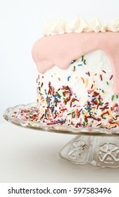 Half Of A Pink Sprinkles Vanilla Birthday Cake On Vintage Glass Platter With White Background