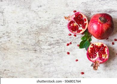 half pomegranate and ripe pomegranate fruit on white wooden rustic background. top view.