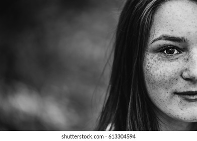Half portrait. Happy young girl with freckles looking at the camera. Black and white.
