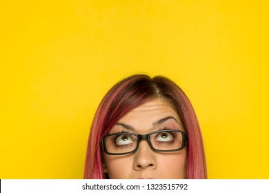 Half portrait of young woman with pink hair and questionable expresion on yellow background