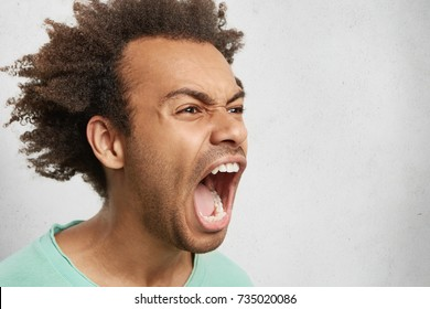 Half profile of aggressive male with dark curly hair, opens mouth widely, screams in panic, finds out horror news, going to cry, being in stressful situation. Frustrated mixed race man yells