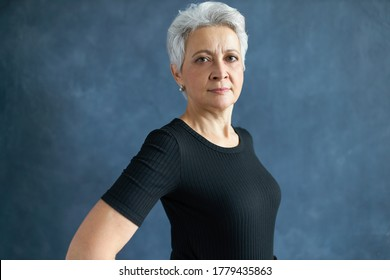 Half profile studio shot of gray haired European woman pensioner in black t-shirt staring at camera with confident look, smiling. Serious mature female posing isolated. People, lifestyle and aging
