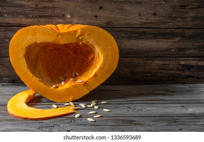 Half a pumpkin in the shape of a heart on an old wooden surface. Vegetarian food  and health concept.