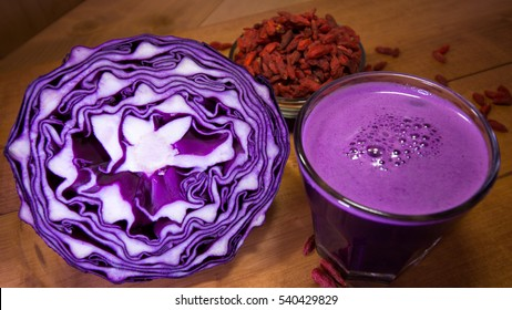 Half of purple/red cabbage and freshly squeezed purple/red cabbage juice; goji berries in the background.