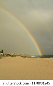 Half rainbow arching over beachside houses in the background ending in the sea with yellow beach in the foreground.